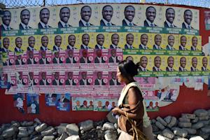A woman walks by election posters of presidential candidates…