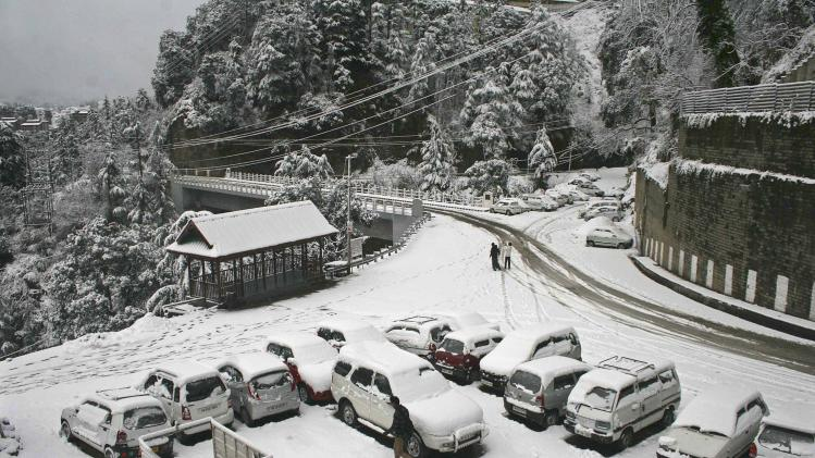 A man walks past snow covered cars after winter's first snowfall in Shimla