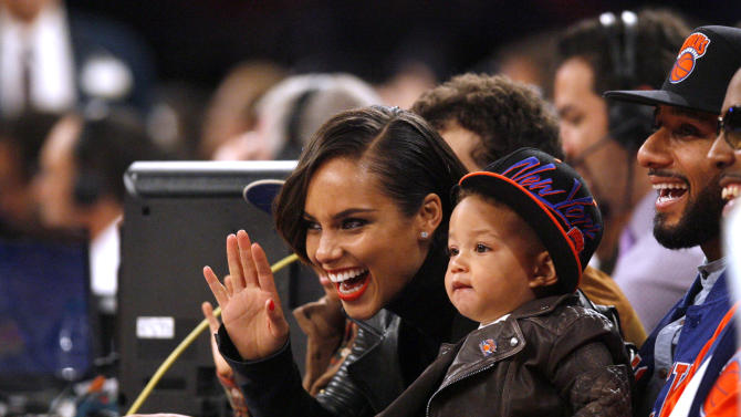 """FILE - In this Nov. 2, 2012 file photo, singer Alicia Keys, left, her son Egypt and her husband Swizz Beatz, right, watch courtside during an NBA basketball game between the New York Knicks and the Miami Heat, in New York. Keys is releasing her fifth album, """"Girl on Fire,"""" on Nov. 27, 2012. It features Frank Ocean, Bruno Mars, Babyface, Emeli Sande, Maxwell, Nicki Minaj, John Legend, her husband Swizz Beatz and their son Egypt. (AP Photo/Jason DeCrow, File)"""