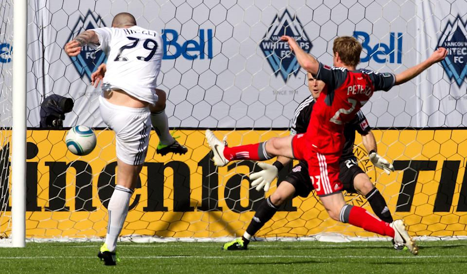 Vancouver Whitecaps' Eric Hassli, from left, scores against Toronto FC goalie Stefan Frei as Toronto's Jacob Peterson, right, defends during the first half of an MLS soccer game in Vancouver, B.C., on Saturday March 19, 2011. (AP Photo/The Canadian Press, Darryl Dyck)