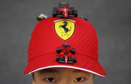 A 10 year old Ferrari fan shows his cap with miniatures of Ferrari's formula one car just after getting an autograph of his favourite driver Raikkonen of Finland, after the qualifying session of the Japanese F1 Grand Prix at the Suzuka Circuit