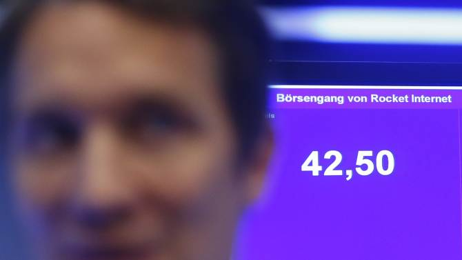 Samwer, CEO of Rocket Internet, a German venture capital group stands past a monitor showing a share price during the initial public offering at the Frankfurt stock exchange