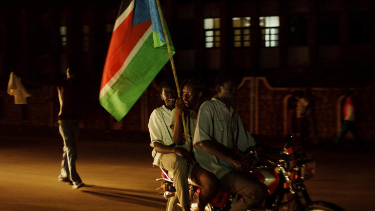 People ride a motorcycle during celebrations ahead of independence in the center of Juba, southern Sudan, late Friday, July 8, 2011. South Sudan became the world's newest nation early Saturday, officially breaking away from Sudan after two civil wars over five decades that cost the lives of millions. (AP Photo/David Azia)