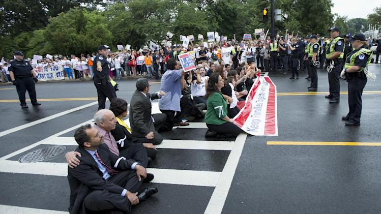 FILE - This Aug. 1, 2013 file photo shows immigration reform supporters blocking a street on Capitol Hill in Washington. For many House conservatives, President Barack Obama's decision to delay a central provision of his health care law has emerged as a major stumbling block _ not to health coverage, but to an immigration bill. (AP Photo/Manuel Balce Ceneta, File)