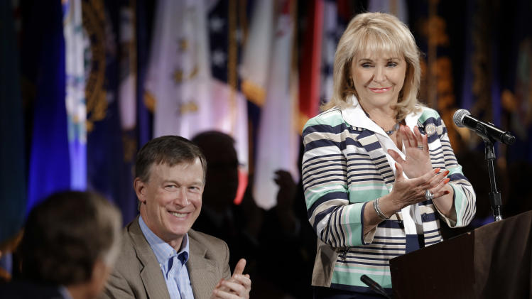 Oklahoma Gov. Mary Fallin, right, and Colorado Gov. John Hickenlooper, center, applaud Tennessee Gov. Bill Haslam, left, during the closing session of the National Governors Association convention Sunday, July 13, 2014, in Nashville, Tenn. (AP Photo/Mark Humphrey)