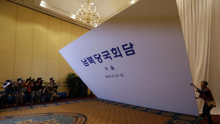 "South Korean workers dismantle a signboard at the venue for the Koreas' first high-level meeting at Grand Hilton Hotel in Seoul, South Korea, Wednesday, June 12, 2013. The Koreas' first high-level talks in years were scrapped a day before they were to begin Wednesday because the sides didn't agree on the delegation leaders, South Korea said. The cancellation deflated tentative hopes that the rivals would improve ties following years of rising hostility. The letters read "" South and North Government Level Talks, Seoul."" (AP Photo/Lee Jin-man)"