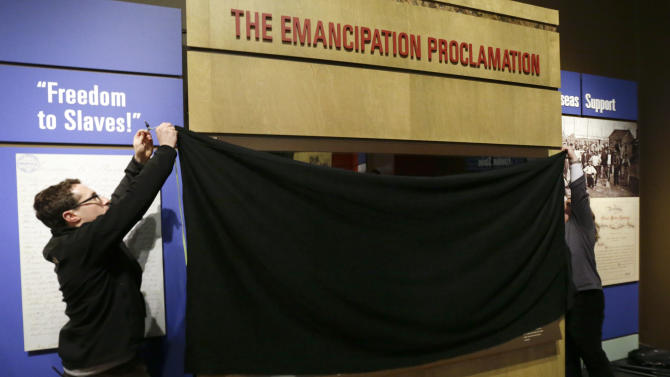 Daniel Falk, left, and Karen Hibbitt, right, both of the National Archives in Washington, D.C., cover the the Emancipation Proclamation following a special viewing at the Tennessee State Museum on Monday, Feb. 11, 2013, in Nashville, Tenn. The document is at the museum in conjunction with an exhibit titled Discovering the Civil War from the National Archives. The papers will only be on view for a total of 72 hours from Tuesday, Feb. 12, and close Monday, Feb. 18, and must be covered and protected from light when not being viewed. (AP Photo/Mark Humphrey)