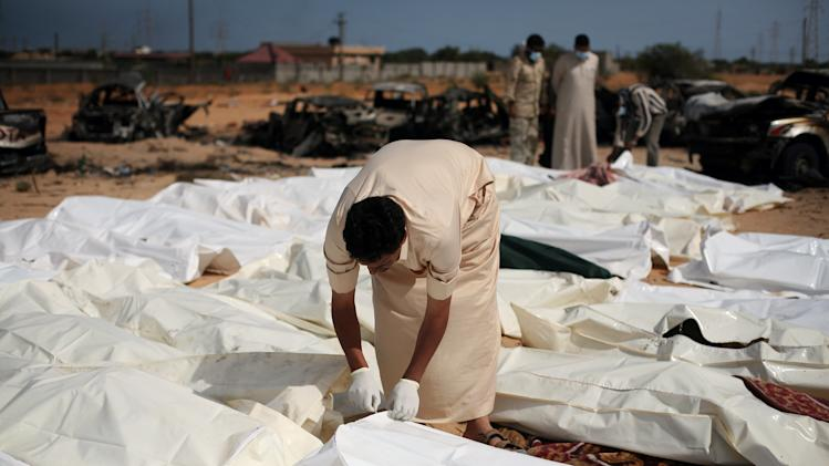 """FILE - In this Oct. 22, 2011 file photo, a revolutionary fighter zips a body bag containing one of nearly 30 bodies of Gadhafi loyalists killed in Sirte, Libya, during the city's fall. Libyan rebels appear to have """"summarily executed"""" scores of fighters loyal to Moammar Gadhafi, and probably the dictator himself, when they overran his hometown in October 2011, according to a Human Rights Watch report released Wednesday, Oct. 17, 2012. (AP Photo/Manu Brabo, File)"""