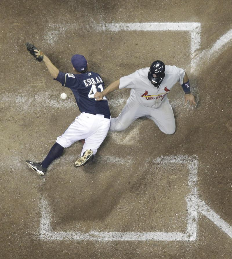 St. Louis Cardinals' Albert Pujols (5) slides safely past Milwaukee Brewers' Marco Estrada (41) to score during the fifth inning of Game 2 of baseball's National League championship series Monday, Oct. 10, 2011, in Milwaukee. (AP Photo/Matt Slocum)