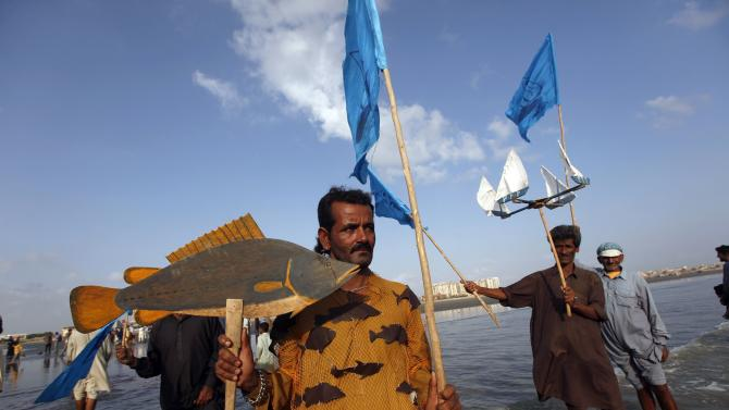 A supporter of the PFF carries a flag and a placard illustrating a fish as they gather to perform a ritual, ahead of the international day of action for rivers and against dams, along Karachi's Clifton beach