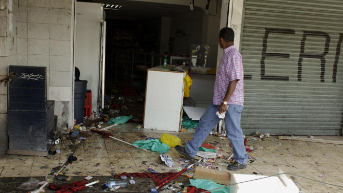 A man walks past a looted store in Panama City, where protesters battled police with sticks and rocks, and police fired tear gas, Friday, Oct. 26, 2012. Panama's government said Friday it will cancel plans to sell state-owned land in a duty-free zone following a week of sometimes violent protests in which a 10-year-old boy and two adults died. Though the land in question is in the port city of Colon, protests spread to Panama City. (AP Photo/Arnulfo Franco)