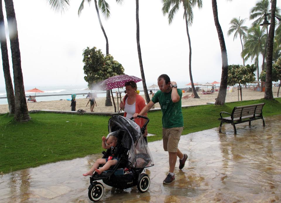 Pedestrians walk along Waikiki beach in Honolulu on Monday, July 29, 2013 as Tropical Storm Flossie approached Hawaii. The storm faded through the morning, but forecasters were still warning residents and tourists to brace for possible flooding, wind gusts, mudslides and big waves. (AP Photo/Audrey McAvoy)