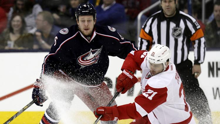 Detroit Red Wings' Tomas Tatar, right, of Slovakia, controls the puck in front of Columbus Blue Jackets' Nikita Nikitin, of Russia, in the second period of an NHL hockey game in Columbus, Ohio, Tuesday, March 11, 2014. (AP Photo/Paul Vernon)