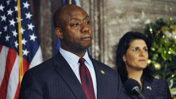 United States Rep. Tim Scott, left, speaks during a news conference as South Carolina Gov. Nikki Haley looks on at the Statehouse on Monday, Dec. 17, 2012, in Columbia, S.C.  Haley announced Scott as Sen. Jim DeMint's replacement in the U.S. Senate during the news conference, making Scott the only black Republican in Congress and the South's first black Republican senator since Reconstruction. (AP Photo/Rainier Ehrhardt)