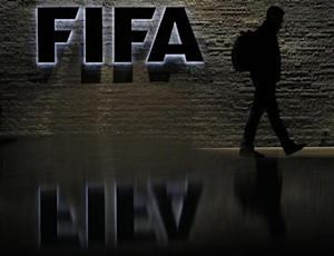 A man is silhouetted as he makes his way past the main entrance of FIFA headquarters in Zurich