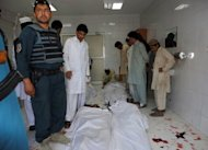 Afghan policeman and civilians gather at a hospital morgue holding the bodies of suicide bombing victims in Khost. A Taliban suicide bomber on a motorbike rammed an Afghan-NATO patrol in the town of Khost on Wednesday, killing 21 people, including three US soldiers, officials said