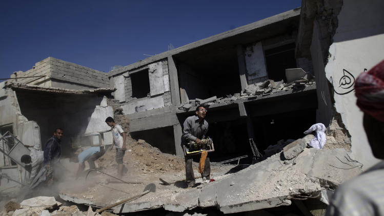 Syrians clear the rubble of a house which was destroyed in government airstrike on Saturday, in Kal Jubrin, on the outskirts of Aleppo, Syria, Sunday, Sept. 16, 2012. (AP Photo/Muhammed Muheisen)