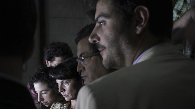 Susana Trimarco, second from left, leaves a court after listening the verdict at the end of the trial of the alleged kidnappers of her daughter Marita Veron in San Miguel de Tucuman, Argentina, Tuesday, Dec. 11, 2012. The 13 defendants, who were charged with kidnapping and forcing Veron to be a prostitute in 2002, were found innocent. (AP Photo/Atilio Orellana)