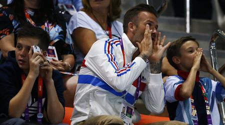 England soccer player David Beckham (C) and his sons Brooklyn (L) and Romeo (R) watch the men's 10m platform final at the London 2012 Olympic Games at the Aquatics Centre