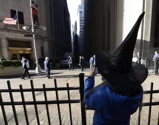 <p>A tourist dressed for Halloween watches as Mayor Michael Bloomberg arrives at the New York Stock Exchange as people return to work on Wall Street. US stocks finished mixed Wednesday as trade resumed after the financial sector was shut down for two days by megastorm Sandy, which blasted New York leaving parts of the city flooded and millions without power.</p>