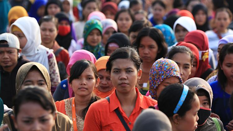 Women workers walk in front of their shoes factory as they return home in Tangerang, Indonesia's Banten province