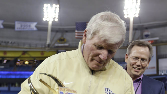 Central Florida coach George O'Leary looks at the trophy after his team defeated Ball State 38-17 during the Beef 'O' Brady's Bowl NCAA college football game Friday, Dec. 21, 2012, in St Petersburg, Fla. (AP Photo/Chris O'Meara)
