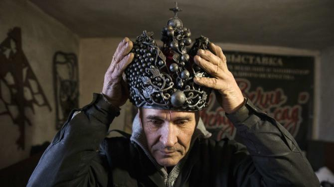 Blacksmith Viktor Mikhalev wears a metal crown made in the likeness of the Imperial Crown of Russia, in his blacksmith's shop in Donetsk
