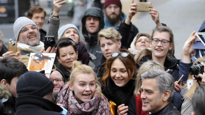 Actor Clooney signs autographs on arrival for photocall during 66th Berlinale International Film Festival in Berlin