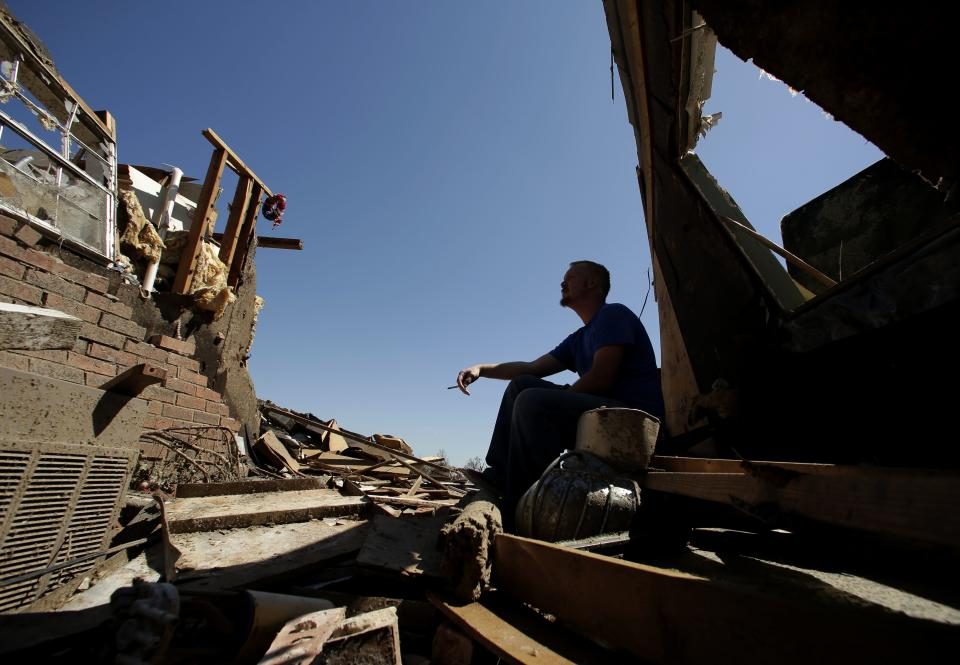 Jesse Edgar takes a break in the shade while helping salvage items at a friend's home Wednesday, May 22, 2013, in Moore, Okla. Cleanup continues two days after a huge tornado roared through the Oklahoma City suburb, flattening a wide swath of homes and businesses. (AP Photo/Charlie Riedel)