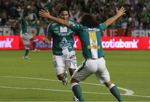 Leon's Carlos Pena, left, celebrates with his teammate Matias Britos after scoring against America during the Mexico league first leg soccer final match in Leon, Mexico, Thursday, Dec. 12, 2013
