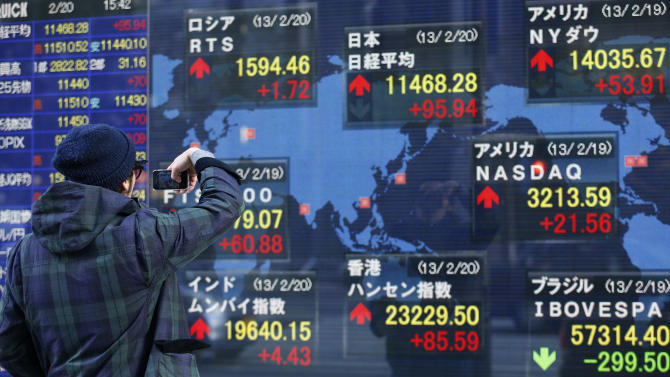 A man takes a photograph of the electronic stock board of a securities firm in Tokyo, Wednesday, Feb. 20, 2013. Asian stock markets picked up stream Wednesday, driven higher by reports that another big corporate takeover might be in the works in the U.S. (AP Photo/Shizuo Kambayashi)