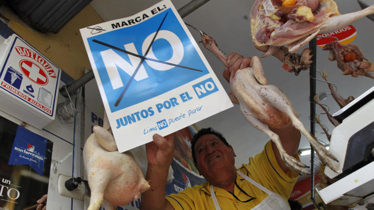 "In this Feb. 16, 2013 photo, chicken vendor Julio Vega places a sign that reads in Spanish ""Check off the 'no.' Together for the 'no.' Lima can't stop,"" against a recall that will attempt to oust Lima's Mayor Susana Villaran, at his shop in a market of Lima, Peru. Villaran, a 63-year-old career human rights defender and the first woman ever elected to manage Peru's capital, will face a recall election on March 17. With her November 2010 election, the left returned to Lima's City Hall for the first time in 23 years. The conservative she defeated, Lourdes Flores, opposes the recall, along with President Ollanta Humala and leading intellectuals, actors, artists and athletes. (AP Photo/Martin Mejia)"