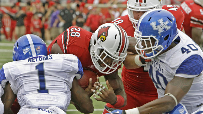 Louisville running back Jeremy Wright (28) muscles through Kentucky defenders Martavius Neloms (1) and Avery Williamson (40) to score the first touchdown of the year during an NCAA college football game at Cardinal Stadium in Louisville, Ky., Sunday, Sept. 2, 2012.  (AP Photo / Garry Jones)