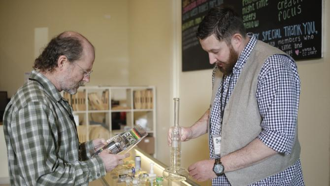 "North Bonneville Mayor Stevens listens while ""bud tender"" Longnecker shows him some products as The Cannabis Corner in North Bonneville"
