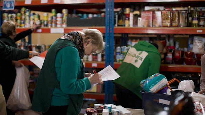 """In this photo taken Friday, April 5, 2013, volunteer Margaret Tobin checks items off a list of food to give out at a food bank in St Luke's Church in the West Norwood area of London, Friday, April 5, 2013. It's possible that official figures on first quarter economic growth, to be released Thursday, could put the country back in recession. It would take the smallest statistical variation to put the figure in negative territory which would place the country in recession, another recession _ the third since the 2008 financial crisis _ and is already being referred to with foreboding in the media as a """"Triple Dip"""". (AP Photo/Matt Dunham)"""