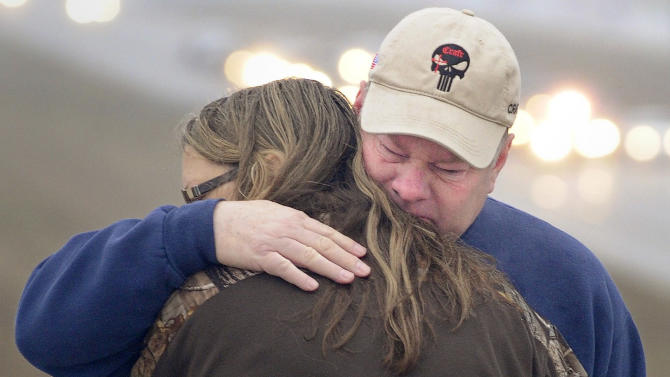 Tracy and Lucinda Larimore, of Henderson, Nv., embrace after the procession for Chris Kyle passes, Tuesday, Feb. 12 2013 in Midlothian, Texas, for the 200-mile journey to Austin, where Kyle will be buried at the Texas State Cemetery.  The Hendersons are friends of Kyle, making the trip to attend the funeral in Arlington yesterday and to pay their respects as the procession passed on Tuesday. Some 7,000 people attended a two-hour memorial service for Kyle at Cowboys Stadium in Arlington on Monday. Kyle and his friend Chad Littlefield were shot and killed Feb 2. at a North Texas gun range. (AP Photo/Star-Telegram, Max Faulkner)