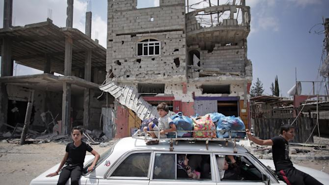 Palestinians in a car with their belongings drive past a destroyed house in Rafah's district of Shawkah in the southern Gaza Strip, Tuesday, Aug. 5, 2014. The attack at the Shawkah district east of the Gaza town of Rafah drew what was by far the heaviest shelling by the Israeli military in the Gaza war, killing nearly 100 people that day alone and instantly unraveling a three-day ceasefire shortly after it came into force. (AP Photo/Khalil Hamra)