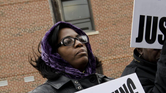 Cecilia Rutherford, 43, of Grand Blanc, joins a group of people holding signs outside of Hurley Medical Center in Flint, Mich. on Tuesday, Feb. 19, 2013, during a protest in response to an African-American nurse's claim that the hospital agreed to a man's request that no black nurses care for his newborn. (AP Photo/The Flint Journal, Lauren Justice) LOCAL TV OUT; LOCAL INTERNET OUT