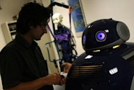 Researcher Pericle Salvini work on a DustClean Robot at the Institute of Biorobotic at Sant'Anna University in Pisa. The dustcart looks like the famous R2-D2 from Star Wars with its laser scanner and location sensors. The idea is that it can work through phone bookings to come to your street at a fixed time to collect your waste