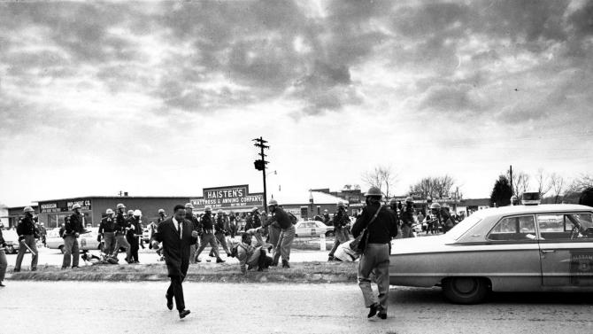 """FILE - In this March 7, 1965, file photo march leader Hosea Williams, left, leaves the scene as state troopers break up the civil rights voter registration march in Selma, Ala., and put John Lewis, center, of the Student Non-violent Coordinating Committee on the ground. Hundreds gathered Sunday, March 3, 2013 for a brunch with Vice President Joe Biden, and thousands were expected Sunday afternoon to march across this bridge in Selma's annual Bridge Crossing Jubilee. The event commemorates the """"Bloody Sunday"""" beating of voting rights marchers by state troopers as they began a march to Montgomery in March 1965. The 50-mile march prompted Congress to pass the Voting Rights Act that struck down impediments to voting by African-Americans and ended all-white rule in the South. (AP Photo/File)"""
