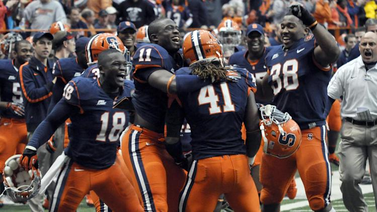 Syracuse's Lewellyn Coker (41) is mobbed by teammates after catching a touchdown pass against Louisville during the fourth quarter of an NCAA college football game in Syracuse, N.Y., Saturday, Nov. 10, 2012. Syracuse won 45-26. (AP Photo/Kevin Rivoli)
