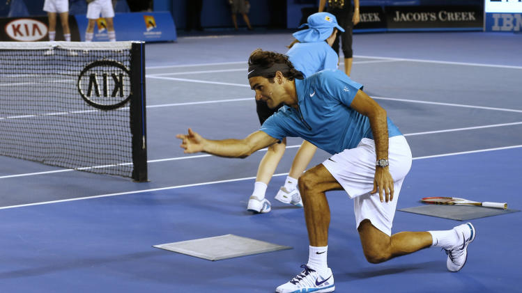 Switzerland's Roger Federer throws the ball along the court as he acts as a ball boy during an exhibition match during the Kids Tennis Day at Melbourne Park ahead of the Australian Open tennis championship in Melbourne, Australia, Saturday, Jan. 12, 2013. (AP Photo/Andy Wong)
