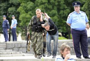 A pro-Russian militant detains a man suspected of spying…