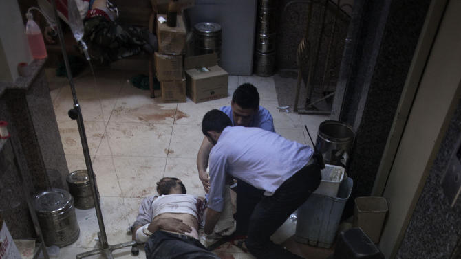 In this Thursday, Oct. 11, 2012 photo, nurses and doctors treat men, wounded by Syrian Army shelling, at Dar al-Shifa hospital in Aleppo, Syria. (AP Photo/Manu Brabo)
