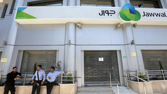 Palestinian Hamas police stand guard in front of the closed doors of Jawwal company's headquarters in Gaza City on June 30, 2015