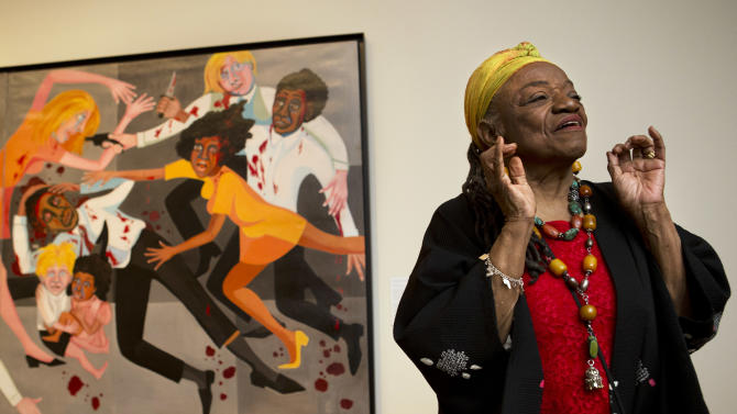 "Artist Faith Ringgold talks about her artwork in front of her painting, ""Die (1967)"" during a press preview of her exhibition, ""American People, Black Light: Faith Ringgold's Paintings of the 1960s"" at the National Museum of Women in the Arts in Washington, Wednesday, June 19, 2013. Ringgold explains her ""confrontational art"" _ vivid paintings whose themes of race, gender, class and civil rights were so intense that for years, no one would buy them. ""I didn't want people to be able to look, and look away, because a lot of people do that with art,"" Ringgold said. ""I want them to look and see. I want to grab their eyes and hold them, because this is America."" (AP Photo/Jacquelyn Martin)"