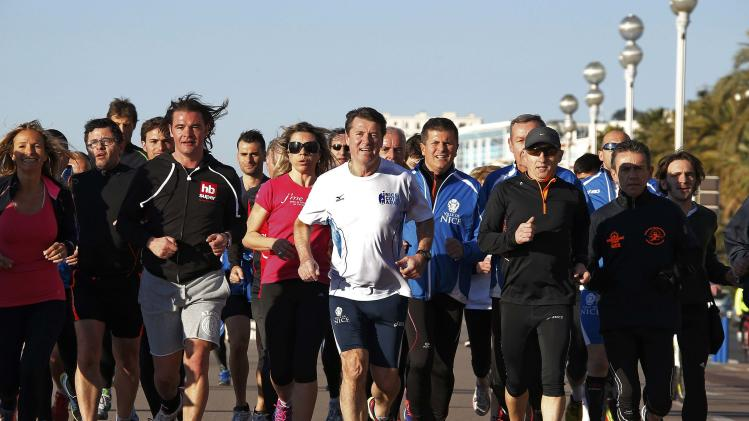 Christian Estrosi, Mayor of Nice and conservative UMP political party candidate for the mayoral election in Nice, jogs with supporters