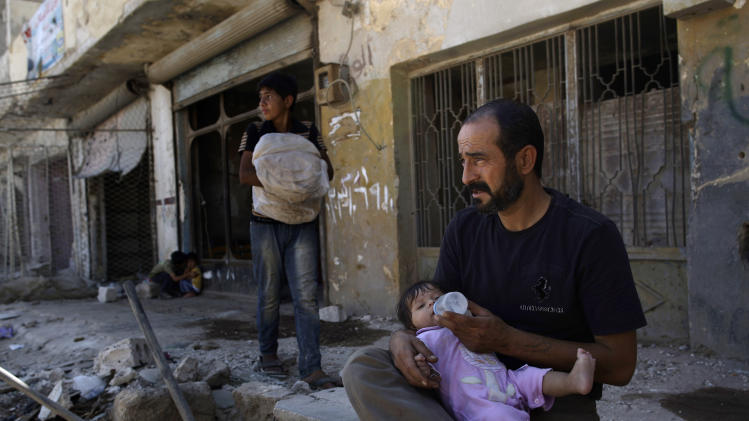 A Syrian man feeds his daughter while sitting in front of his partly damaged house, in Azaz, on the outskirts of Aleppo, Syria, Tuesday, Aug. 28, 2012. (AP Photo/Muhammed Muheisen)