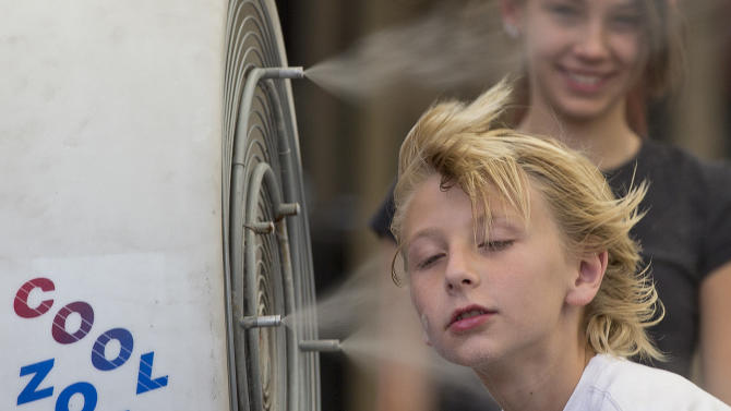 Ten-year-old Easton Martin, of Mesa, Ariz., stops to cool off in a misting fan while walking along The Strip with his family, Friday, June 28, 2013 in Las Vegas. A blazing heat wave expected to send the mercury soaring to nearly 120 degrees in Phoenix and Las Vegas settled over the West on Friday, threatening to ground airliners and raising fears that people and pets will get burned on the scalding pavement. (AP Photo/Julie Jacobson)