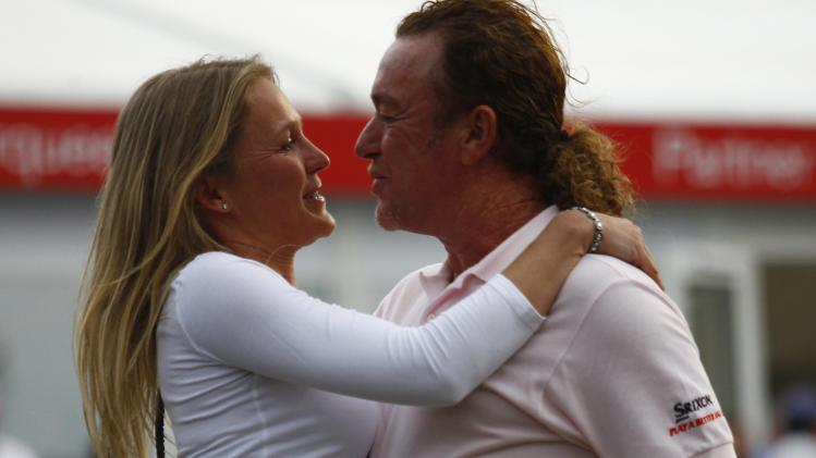 Defending champion Jimenez of Spain is hugged by girlfriend Styblo after winning European Tour Hong Kong Open golf tournament